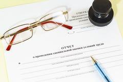 Document in Russisch Rapport over de speciale beoordeling van arbeidsvoorwaarden, glazen, druk en pen op de boekhoudingslijst royalty-vrije stock fotografie