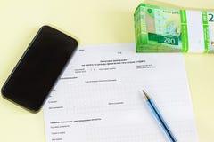 Document in Russische Belastingsverklaring op persoonlijke inkomstenbelasting, pen, smartphone en geld voor belastingsbetaling royalty-vrije stock foto's