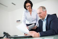 Document sérieux de People Discussing Over d'homme d'affaires dans le bureau image stock