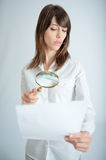 Document scrutiny. Young woman inspecting closely a document through a magnifying glass Royalty Free Stock Photos