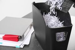 Document shredder with paper shreds on table. Closeup Stock Photo