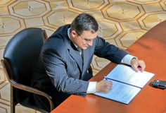 Document signing. The businessman at office signs the document royalty free stock image