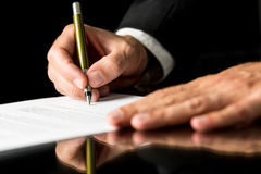 Document signing. Closeup of male hand signing legal or insurance document on black desk with reflection royalty free stock images