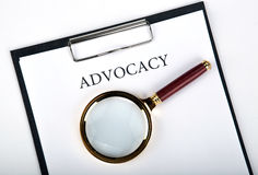Document with the title of advocacy. With loupe close up royalty free stock images