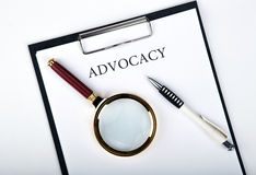 Document with the title of advocacy. With pen, loupe close up stock photos