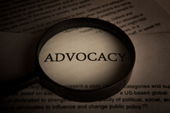 Document with the title of advocacy under a magnifying glass Royalty Free Stock Photo