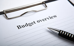 Document with title budget overview and pen. Close up stock images