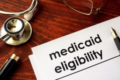 Document with title medicaid eligibility. Document with title medicaid eligibility on a desk Royalty Free Stock Photo