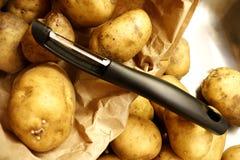 Document zak met aardappels en een zwart schilmesje stock afbeelding