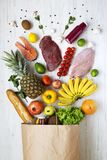 Document zak van diverse gezonde producten op witte houten achtergrond, van hierboven Natuurlijke voeding Vlak leg Stock Foto's