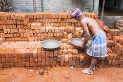 Documentair Redactiebeeld De mens neemt bakstenen in een grote plaat Royalty-vrije Stock Fotografie