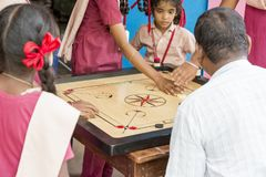Documentary editorial image. Children playing carrom at the table. the concept of childhood and board games, brain development and Stock Image