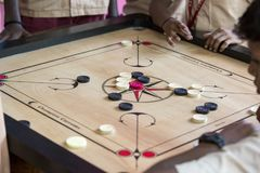 Documentary editorial image. Children playing carrom at the table. the concept of childhood and board games, brain development and Royalty Free Stock Image