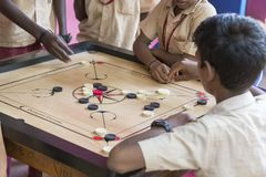 Documentary editorial image. Children playing carrom at the table. the concept of childhood and board games, brain development and