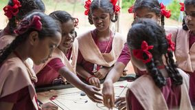 Documentary editorial image. Children playing carrom at the table. the concept of childhood and board games, brain development and Royalty Free Stock Photo