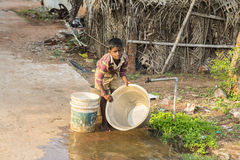 Documentary editorial image,Poverty in the street India. Documentary editorial image. Pondicherry, Tamil Nadu, India - May 15 2014. Very poor boy washing dishes Royalty Free Stock Photography