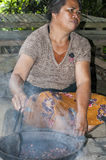 Documentary editorial image. Woman roasting cocoa. Ubud, Bali, Indonesia - July 27, 2013. Woman farmer sitting on the floor, roasting cocoa in traditional plates Royalty Free Stock Photography