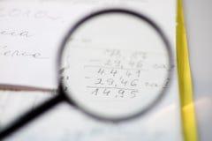 Documenten, berekeningen en berekeningen door vergrootglas Stock Foto's
