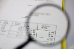 Documenten, berekeningen en berekeningen door vergrootglas Stock Fotografie