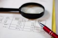 Documenten, berekeningen en berekeningen door vergrootglas Royalty-vrije Stock Afbeeldingen