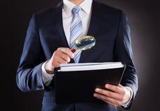 Documenti d'esame dell'uomo d'affari con la lente d'ingrandimento immagine stock libera da diritti