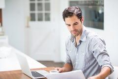 Documenti della lettura del giovane mentre sedendosi allo scrittorio con il computer portatile Fotografie Stock