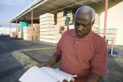 Documenti della lettura del lavoratore del magazzino immagine stock libera da diritti