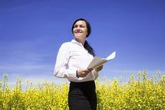 Documenti della tenuta della donna di affari fra i fiori ed il blu gialli Immagini Stock Libere da Diritti