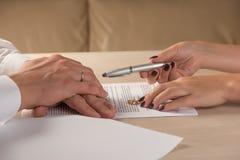 Documenti di firma di divorzio del marito e della moglie, fede nuziale di ritorno della donna fotografia stock libera da diritti