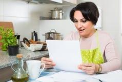 Documenti di riempimento di attività bancarie della donna e sorridere nella cucina immagine stock