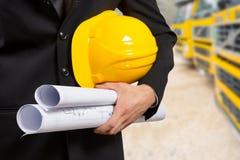 Documenti e cappello di progetto della tenuta della mano dell'architetto Immagine Stock Libera da Diritti