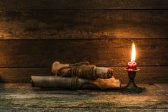 Documenti masterizzati e una candela bruciante su una vecchia, tavola consumata fotografie stock
