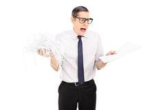 Documenti tagliuzzati tenuta colpiti dell'uomo d'affari Immagini Stock