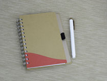 Documenting days and night. A notebook with a pen on a textured background Royalty Free Stock Photos