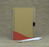 Documenting days and night. A notebook with a pen on a textured background Stock Photography