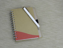 Documenting days and night. A notebook with a pen on a textured background Stock Photo