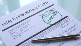 Documento approvato di politica dell'assicurazione malattia, guarnizione dei bolli della mano su carta ufficiale stock footage