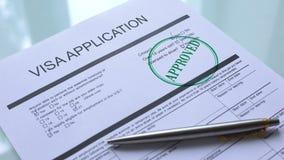 Documento aprobado, mano de la solicitud de visado que sella el sello en el primer de papel oficial metrajes