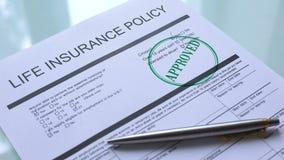 Documento aprobado póliza de seguro de vida, mano que sella el sello en el papel oficial almacen de video