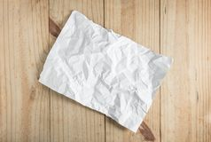 Documento arrugado blanco sobre fondo de madera Foto de archivo