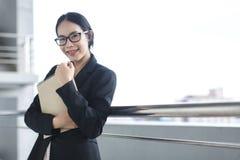 Documento asiático joven del fichero de tenencia del traje del desgaste de la mujer de negocios foto de archivo libre de regalías