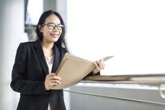 Documento asiático joven del fichero de tenencia del traje del desgaste de la mujer de negocios foto de archivo