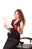 Documento atrativo da leitura da mulher de negócios ao apreciar uma chávena de café Fotografia de Stock
