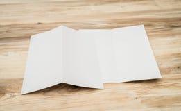 Documento blanco plegable de la plantilla sobre la textura de madera Imagenes de archivo