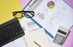 Documento cartaceo di rapporto del grafico del grafico finanziario e commerciale con la carta aperta del taccuino del calcolatore immagine stock