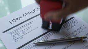 Documento in corso, mano di applicazione di prestito che timbra guarnizione sulla carta ufficiale, primo piano stock footage
