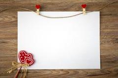 Documento de Blanc sobre el backgrownd de madera con el corazón imagen de archivo libre de regalías