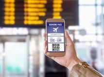 Documento de embarque en teléfono móvil Mujer que sostiene smartphone en aeropuerto con el boleto moderno en la pantalla Foto de archivo libre de regalías