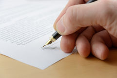 Documento de firma del hombre de negocios con la pluma Imagen de archivo libre de regalías