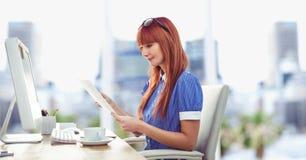 Documento de la lectura de la empresaria en el escritorio en oficina Foto de archivo